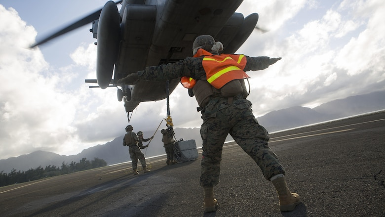 "Pfc. Jose Camacho, a landing support specialist with Transportation Services Company, Combat Logistics Battalion 3, guides a CH-53E Super Stallion helicopter from Marine Heavy Helicopter Squadron 463, nicknamed ""Pegasus,"" during external lift training at Landing Zone West Field at Marine Corps Air Station Kaneohe Bay, Hawaii, March 8, 2017. This training improves proficiency for the pilots when moving supplies while Marines on the ground conditioned themselves to safely prepare dual and single load lifts."