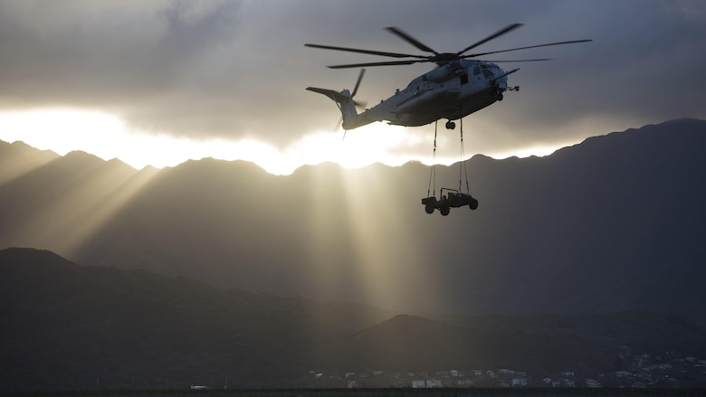 A CH-53E Super Stallion helicopter assigned to Marine Heavy Helicopter Squadron 463, carries a Humvee during an external lift training at Landing Zone West Field at Marine Corps Air Station Kaneohe Bay, Hawaii, March 8, 2017. This training improves proficiency for the pilots when moving supplies while Marines on the ground conditioned themselves to safely prepare dual and single load lifts.
