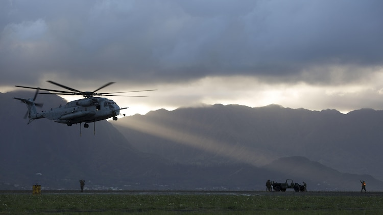 "A landing support specialist with Transportation Services Company, Combat Logistics Battalion 3, guides a CH-53E Super Stallion helicopter assigned to Marine Heavy Helicopter Squadron 463, nicknamed ""Pegasus,"" during external lift training at Landing Zone West Field at Marine Corps Air Station Kaneohe Bay, Hawaii, March 8, 2017. This training improves proficiency for the pilots when moving supplies while Marines on the ground conditioned themselves to safely prepare dual and single load lifts."