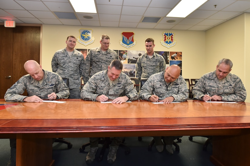 U.S. Air Force Col. Robert Lyman, 628th Air Base Wing commander, left-center, with Chief Master Sgt. Todd Cole, 628th Air Base Wing command chief, left, Col. Jimmy Canlas, 437th Airlift Wing commander, right-center, Chief Master Sgt. Kristopher Berg, 437th Airlift Wing command chief, right, donate to the Air Force Assistance Fund March 13, 2017 at Joint Base Charleston. The AFAF campaign is a fundraising event taking place from March 6 through April 14, 2017 here. During this time, money will be raised through various fundraising events. The large thermometer signs located on base indicate the progress toward reaching this year's goal of $50,950 and 100 percent contact.