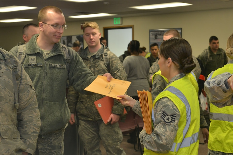 Staff Sgt. Michael Backus, 5th Aircraft Maintenance Squadron, 5th Aircraft Maintenance Squadron instrument and flight control systems craftsman, receives medical documents from Staff Sgt. Jessica Washington, 5th Medical Operations Squadron public health technician at Minot Air Force Base, N.D., March 9, 2017. More than 400 Airmen from the 5th Bomb Wing recently deployed to the Middle East, in support of U.S. Central Command's Operation Inherent Resolve. (U.S. Air Force photo/Airman 1st Class Jessica Weissman)
