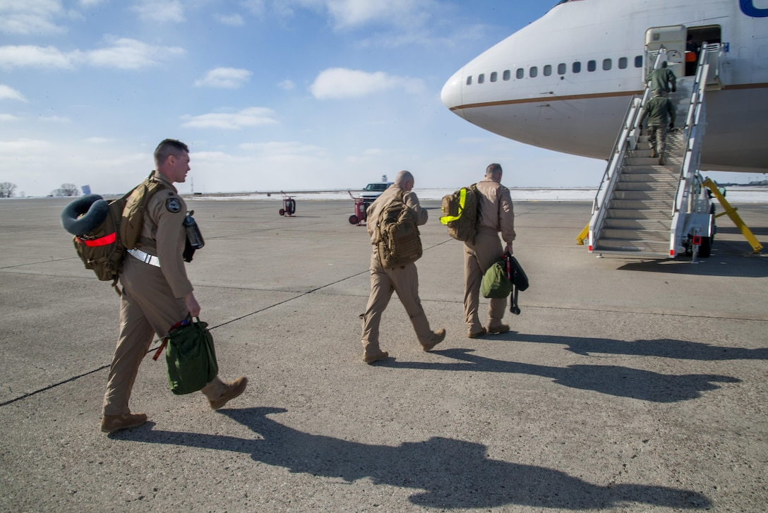 Minot Airmen board a plane during a mass deployment at Minot Air Force Base, N.D., March 9, 2017. Airmen deploy to assure allies, deter adversaries and defeat our enemies. (U.S. Air Force photo/Senior Airman Christian Sullivan)