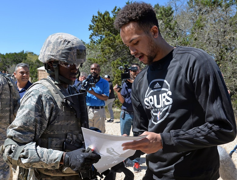 Kyle Anderson of the San Antonio Spurs signs a Spurs banner for a fan during training at Joint Base San Antonio-Camp Bullis March 14.