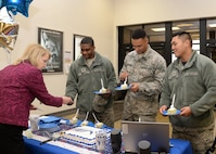 Kathleen Vaillancourt, Airman and Family Readiness Center community readiness consultant, serves cake to Staff Sgt. Kadeem Smith, Airman 1st Class Hector Martinez and Senior Airman Fidel Ababa, all assigned to the 66th Medical Squadron, during an Air Force Aid Society celebration at the base exchange March 10. The event was held to celebrate 75 years of helping Airmen. (U.S. Air Force photo by Linda LaBonte Britt)