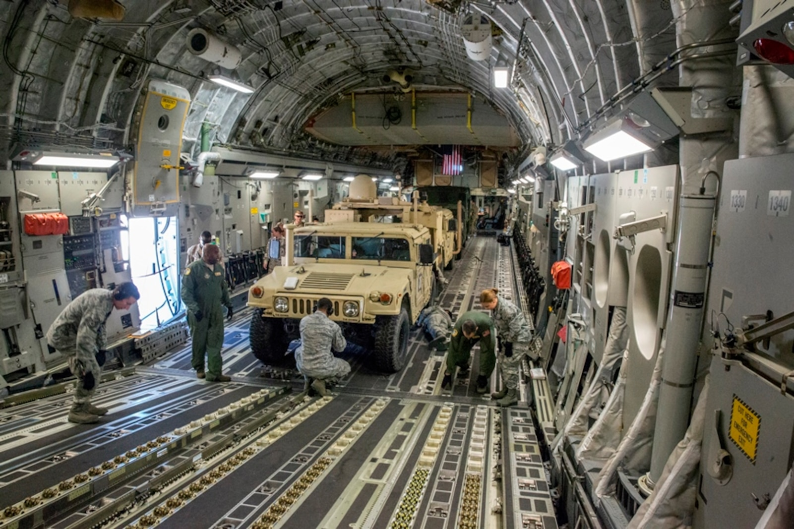 Airmen with 50th Aerial Port Squadron, 452nd Air Mobility Wing, strap down three Marine Corps High Mobility Multipurpose Wheeled Vehicles (HMMWV) that are parked in the loading bay of an Air Force C-17 Globemaster III aircraft during Strategic Mobility Exercise on March Air Force Reserve Base, Calif., March 12, 2017. STRATMOBEX is a training exercise conducted by the 1st Marine Logistics Group in order to maintain readiness and sharpen skills needed to rapidly deploy personnel and equipment on a large scale.