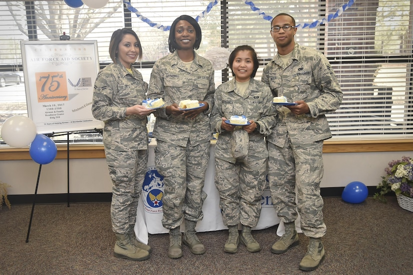 Airmen pose for a photo during an event celebrating the Air Force Aid Society's 75th Anniversary at the Airman and Family Readiness Center here, March 10, 2017. The AFAS is a private non-profit organization working to provide relief to Air force members and their families in financial distress and to assist in their pursuit of higher education goals. There are four charities that service members can donate to as part of the Air Force Assistance Fund campaign (AFAF). Those interested in the AFAF campaign have until April 14 to make pledges.