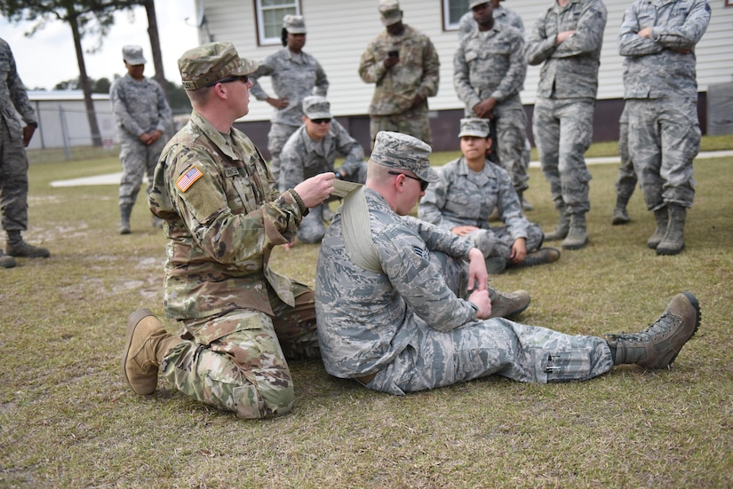 Army Sergeant Wesley Brantley, South Carolina Medical Detachment pre-mobilization assistance staff member, (left) applies a field dressing to Senior Airman Joseph C Kohnke, 628th Civil Engineer Squadron, engineer, (right) at McCrady Training Center March 8, 2017. Thirty Airmen from Joint Base Charleston attended the weeklong war skills training that taught land navigation, combat casualty care, improvised explosive device identification procedures, hand-to-hand combat skills and team building exercises.