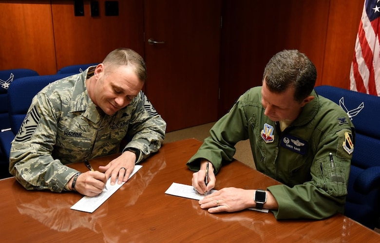 Chief Master Sgt. Shane Wagner, 4th Fighter Wing command chief, and Col. Christopher Sage, 4th FW commander, sign their donation forms for the 2017 Air Force Assistant Fund. The AFAF is an Air Force-wide campaign that generates donations for four different charities: Air Force Villages, Air Force Enlisted Villages, The General and Mrs. Curtis E. Lemay Foundation and the Air Force Aid Society. (U.S. Air Force photo by Airman 1st Class Kenneth Boyton)