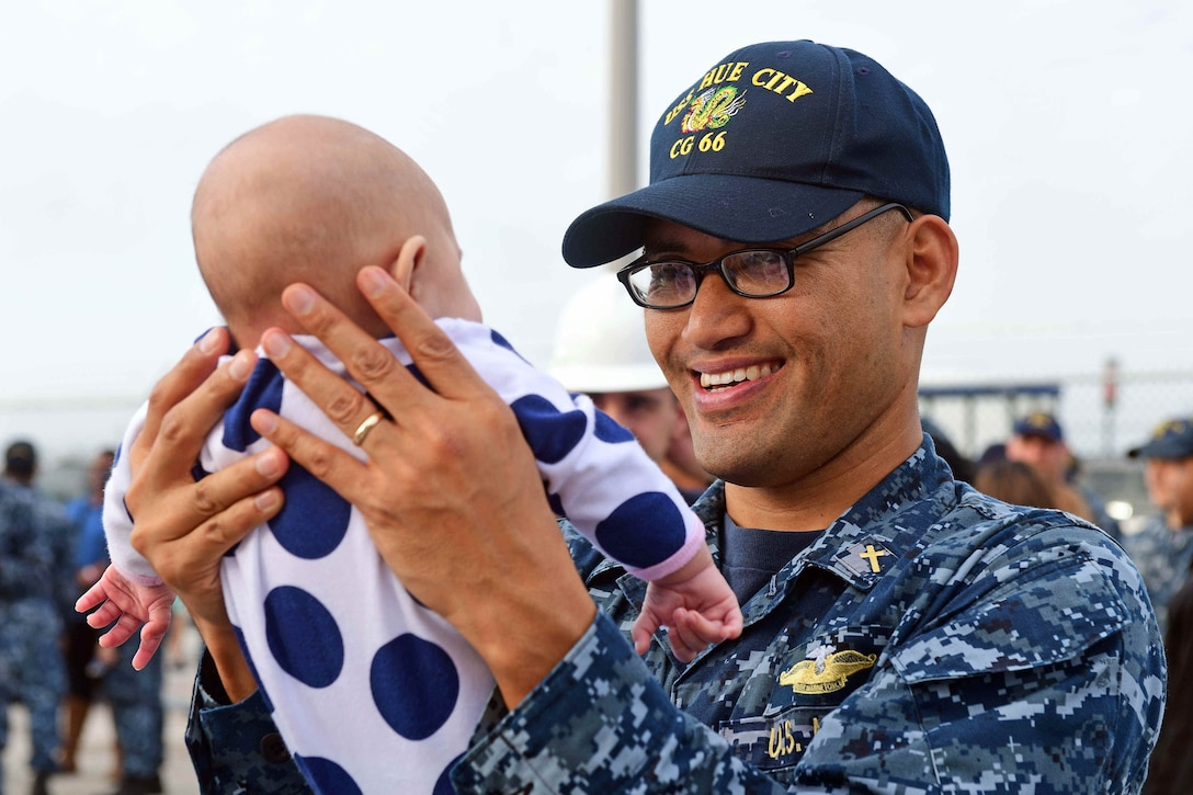 Navy Lt. Pon Chanthaphon holds his infant daughter