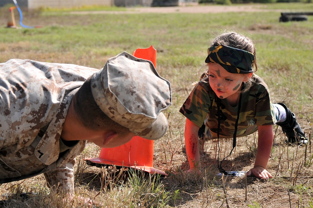 A child performs push-ups with a Marine
