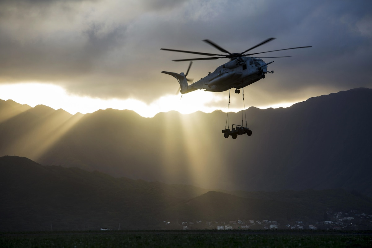 A helicopter carries a Humvee as the sun's rays spread over a mountain range.