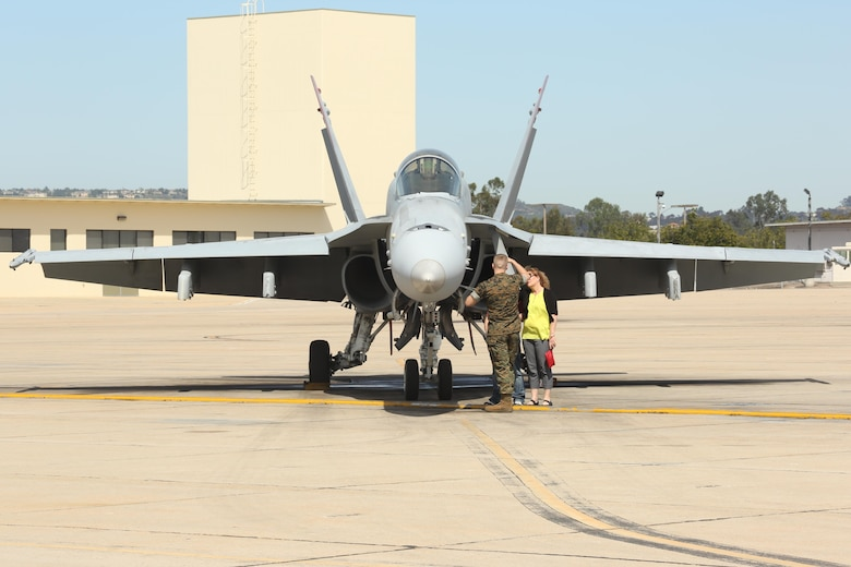 """A Marine with Marine Fighter Attack Squadron (VMFA) 232 """"Red Devils"""" shows an F/A-18C Hornet to his family at Marine Corps Air Station Miramar, Calif., March 14. More than 150 Marines with VMFA-232 deployed to participate in the unit deployment program at MCAS Iwakuni, Japan, March 14. (U.S. Marine Corps photo by Lance Cpl. Jake M.T. McClung/Released)"""