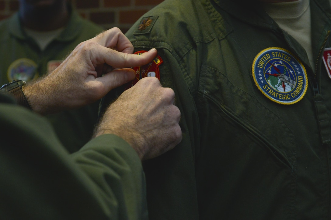 A 740th Missile Squadron operator receives a 48-hour alert pin at Minot Air Force Base, N.D., March 15, 2017. On March 6, a winter storm caused 91st Missile Wing Intercontinental Ballistic Missile operators to stay an extra night until a crew could safely replace them. (U.S. Air Force photo/Airman 1st Class Jessica Weissman)
