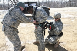 FORT MCCOY, Wis. - U.S. Army Reserve Soldiers with 327th Engineer Company, 416th Theater Engineer Command, assist another 327th Eng. Co. Soldier with his gunners harness prior to completing the blank-fire range during Operation Cold Steel at McCoy, Wis., March 13, 2017. Operation Cold Steel is the U.S. Army Reserve's crew-served weapons qualification and validation exercise to ensure that America's Army Reserve units and soldiers are trained and ready to deploy on short-notice and bring combat-ready and lethal firepower in support of the Army and our joint partners anywhere in the world. (U.S. Army Reserve photo by Staff Sgt. Debralee Best, 84th Training Command)