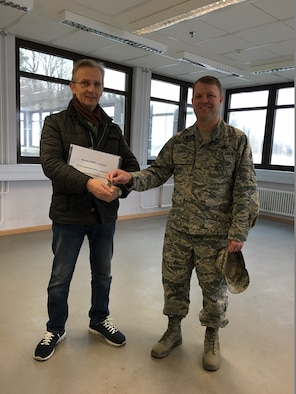 Chief Master Sgt. Jonathan Eason, former 606th Air Control Squadron chief enlisted manager Detachment 1, hands over the keys to building 345, the former location of the 606th ACS to Josef Ehlenz, 52nd Civil Engineer Squadron base property specialist, at Spangdahlem Air Base, Germany, March 8, 2017. (Courtesy photo)