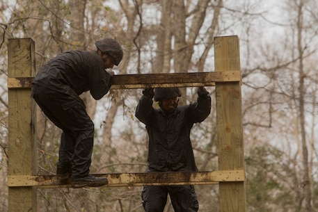 Marines climb over an obstacle during an endurance course at the Battle Skills Training School on Camp Lejeune, N.C., Mar. 10, 2017. The course is designed to improve and test Marines on their ability to work together through the challenging obstacles.  The Marines are with 8th Engineer Support Battalion. (U.S. Marine Corps photo by Pfc. Abrey Liggins)