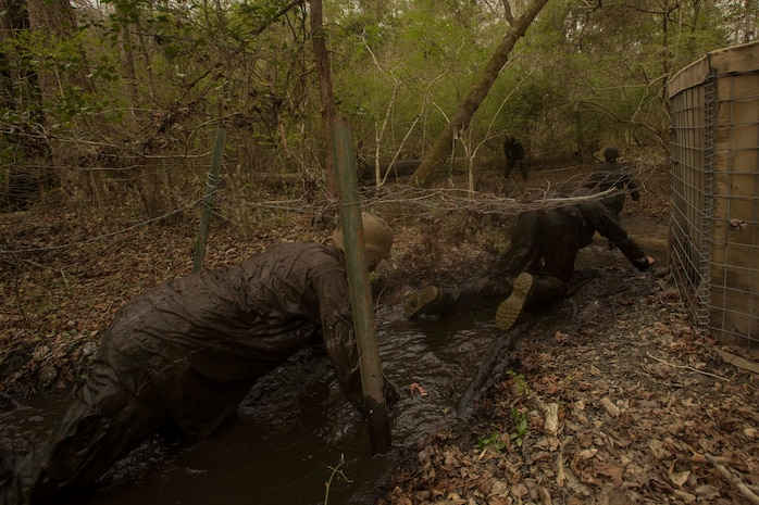 Marines crawl in muddy water during an endurance course at the Battle Skills Training School on Camp Lejeune, N.C., March. 10, 2017. The course is designed to improve and test Marines on their ability to work together through the challenging obstacles.  The Marines are with 8th Engineer Support Battalion. (U.S. Marine Corps photo by Pfc. Abrey Liggins)