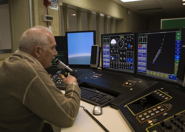 Glynn Breuer, 5th Operations Support Squadron contractor system operator, uses a microphone to communicate with instructors in the B-52H Stratofortress weapons system trainer during a simulated flight at Minot Air Force Base, N.D., March 8, 2017. Breuer maintains and operates the WST for base aircrews. (U.S. Air Force photo/Airman 1st Class Alyssa M. Akers)