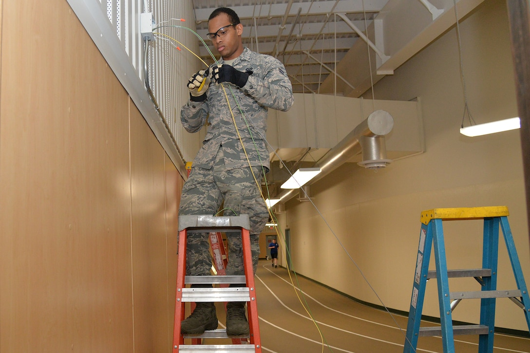 Airman 1st Class Kristoff Chin, 341st Civil Engineer Squadron electrical systems apprentice, replaces emergency lights in the fitness center March 13, 2017, at Malmstrom Air Force Base, Mont. The 341st Civil Engineer Squadron electrical shop will be replacing more than 12,000 fluorescent light fixtures with LED lamps at nine facilities on base. (U.S. Air Force photo/Airman 1st Class Daniel Brosam)