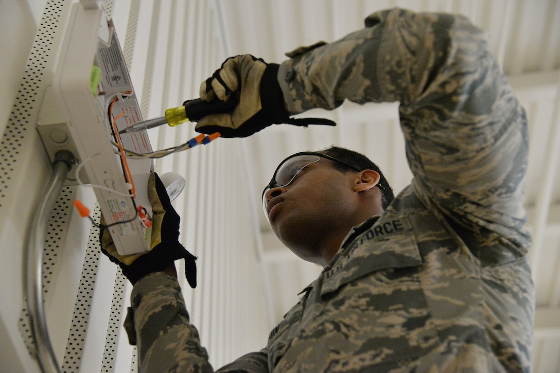 Airman 1st Class Kristoff Chin, 341st Civil Engineer Squadron electrical systems apprentice, fixes an emergency light in the fitness center March 13, 2017, at Malmstrom Air Force Base, Mont. The electrical team is replacing more than 12,000 lamps on base at nine facilities with LEDs, and they have already completed three of the nine buildings. (U.S. Air Force photo/Airman 1st Class Daniel Brosam)