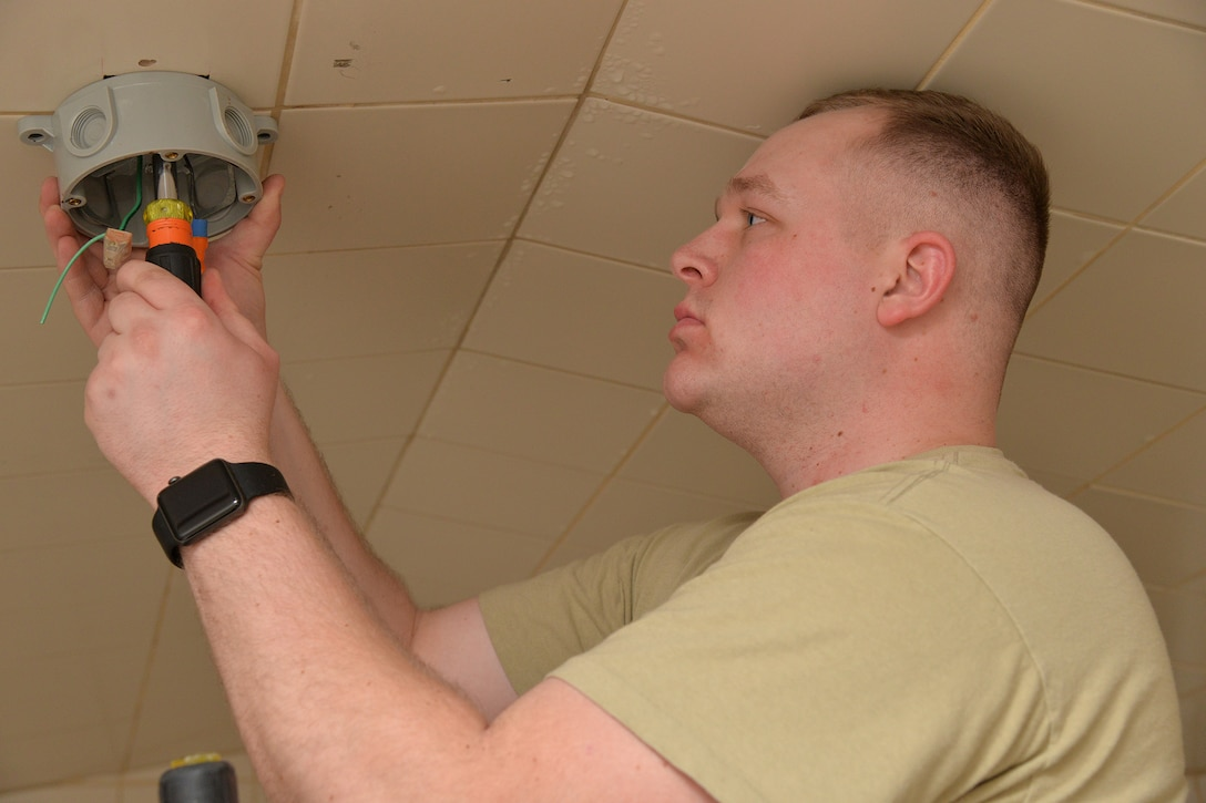 Senior Airman Dillon Halbach, 341st Civil Engineer Squadron electrical systems journeyman, repairs a light fixture inside the fitness center March 13, 2017, at Malmstrom Air Force Base, Mont. LED lights require half the wattage of currently used lights and also have a lamp life of 50,000 hours, nearly five times the life of fluorescent lights. (U.S. Air Force photo/Airman 1st Class Daniel Brosam)
