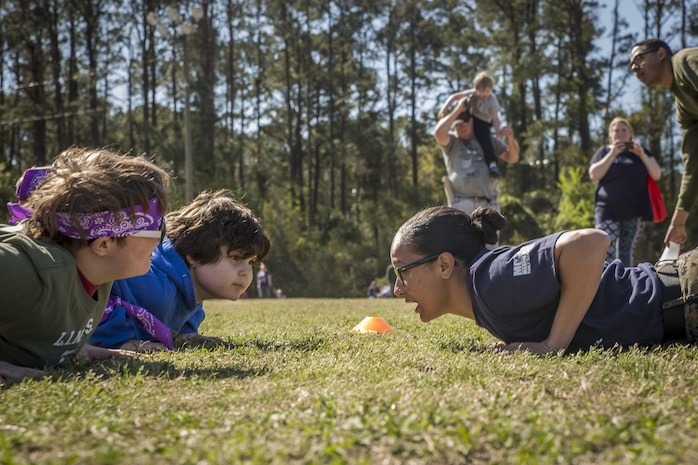Sgt. Jasmine Smith encourages children during a modified Combat Fitness Test at Mini Marines aboard Marine Corps Air Station, Mar. 11. The event, hosted by Marine Corps Community Services Beaufort, to promote a camaraderie and a family atmosphere for Marines and their children. It also gives children a view into what their parents do at work. Smith is a training non-commissioned officer with Marine Aviation Logistics Squadron 31, Marine Aircraft Group 31.