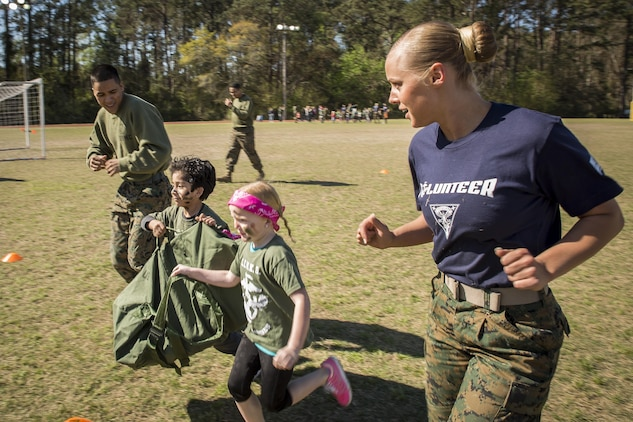 Marines guide children through a modified Combat Fitness Test during Mini Marines aboard Marine Corps Air Station, Mar. 11. The Marine Corps Community Services event is held for families and children to show them what their parents do at work. The Marines are stationed aboard MCAS Beaufort.