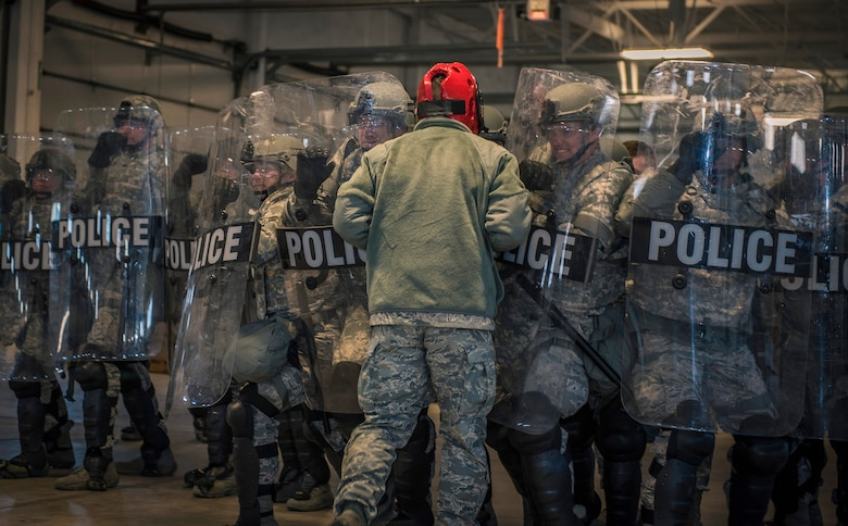 Security forces specialists assigned to the 182nd Security Forces Squadron, Illinois Air National Guard, initiate a maneuver to apprehend a simulated combative rioter during civil disturbance training in Peoria, Ill., March 4, 2017. The squadron trains in confrontation management as part of the Air National Guard's mission to be the first choice for homeland operations. (U.S. Air National Guard photo by Tech. Sgt. Lealan Buehrer)