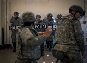 Security forces specialists assigned to the 182nd Security Forces Squadron, Illinois Air National Guard, react to simulated rioters throwing baseballs at them during civil disturbance training in Peoria, Ill., March 4, 2017. The squadron trains in confrontation management as part of the Air National Guard's mission to be the first choice for homeland operations.