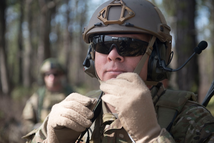 U.S. Air Force Maj. Ryan Schenk, 621st Mobility Support Operations Squadron air mobility liaison officer assigned to the 101st Airborne Division at Fort Campbell, Ky., adjusts his helmet while waiting for the airfield to be cleared during a mobility exercise called WAREX at Joint Base McGuire-Dix-Lakehurst, N.J., March 13, 2017. AMLOs are highly experienced, U.S. Air Force pilots and navagators embedded with Army and Marine units, in-garrison and deployed. (U.S. Air Force photo by Tech. Sgt. Gustavo Gonzalez/RELEASED)