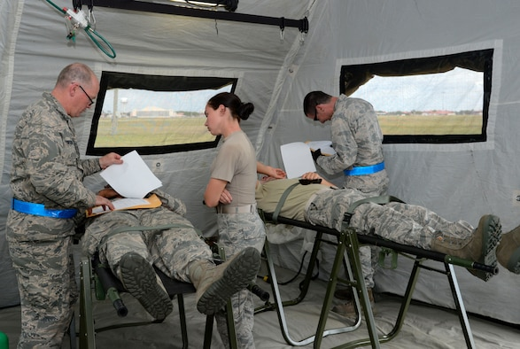 Two nurses and a medical technician provide patient care to simulated injuries during an aeromedical evacuation exercise at MacDill Air Force Base, Fla., March 12, 2017. As a role two staging facility, an En Route Patient Staging System team secures and stabilizes any first responder care done in the field while simultaneously preparing patients for travel to a more advanced form of care. (U.S. Air Force photo by Senior Airman Tori Schultz)