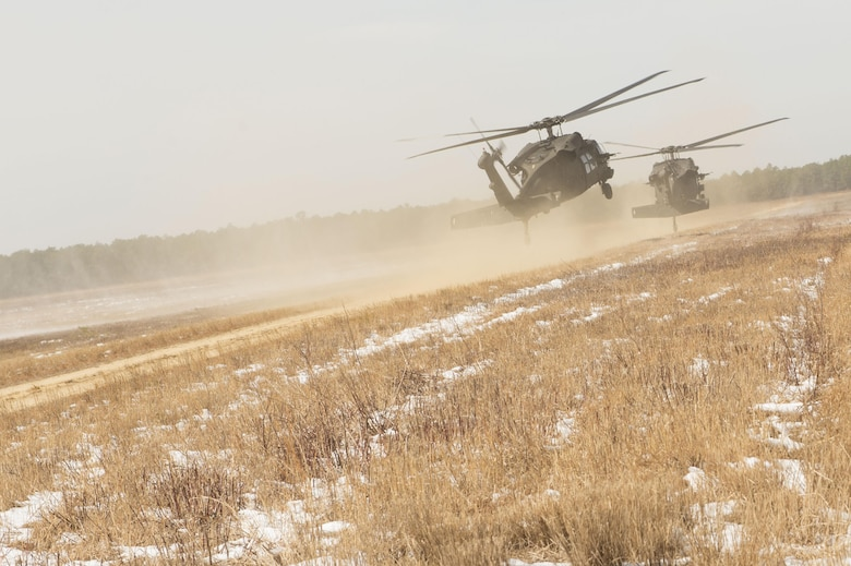 Two U.S. Army UH-60 Black Hawks land during a mobilty exercise called WAREX at Joint Base McGuire-Dix-Lakehurst, N.J., March 13, 2017. The WAREX is conducted to validate seamless Joint Task Force-Port Opening hand-off from airfield seizure forces and support the Army ground forces exercise tasks that are also being evaluated. (U.S. Air Force photo by Tech. Sgt. Gustavo Gonzalez/RELEASED). (U.S. Air Force photo by Tech. Sgt. Gustavo Gonzalez/RELEASED)