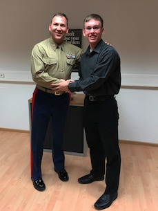 Alex Voyer, a senior in Wiesbaden High School, Wiesbaden, Germany, shakes hands with U.S. Marine Lt. Col. Gregory Wilson, the officer-in-charge of the Marine liaison team of Landstuhl Regional Medical Center, at the Marine Forces Europe / Africa Headquarters on United States Army Garrison Stuttgart, following his swearing-in, Feb. 8, 2017. Voyer is one of the first two applicants to enlist in the Marine Corps since the Marines started offering enlistment opportunities in Europe.