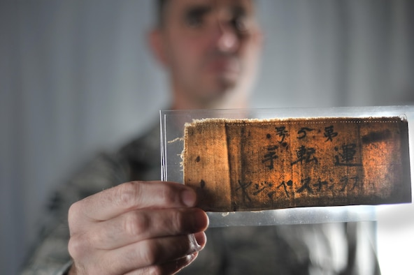 Chief Master Sgt. Jake Higginbotham, 70th Intelligence, Surveillance and Reconnaissance Wing command chief, holds the arm band that Master Sgt. retired Francis M. Bania wore while imprisoned after the Bataan Death March.  (U.S. Air Force photo/Staff Sgt. Alexandre Montes)