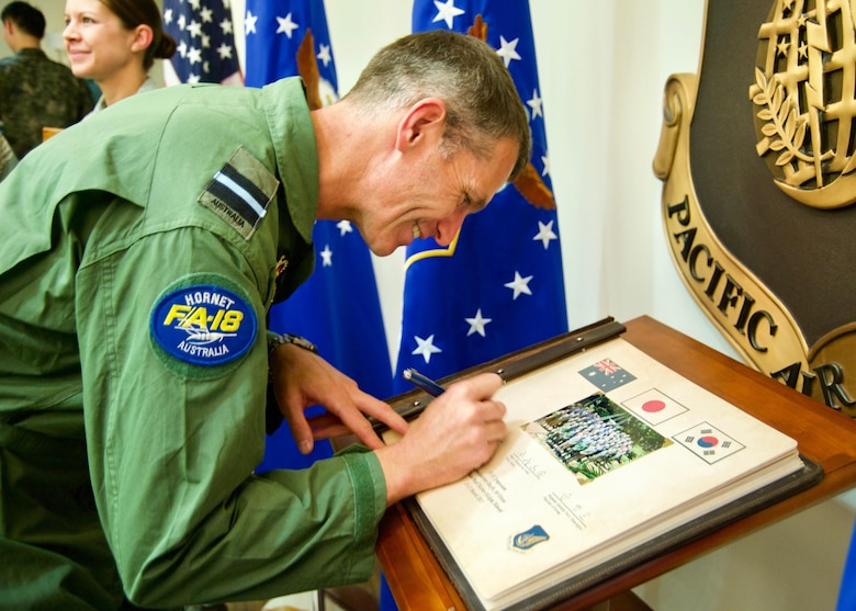 Royal Australian Air Force Air Cdre Robert Chipman, General Planning Capability director, signs Pacific Air Forces' guest book during the Pacific F-35 Symposium at Joint Base Pearl Harbor-Hickam, Hawaii, March 15, 2017. The symposium is a PACAF-hosted event that brings together the four Pacific members of the F-35 program: Japan, Australia, the Republic of Korea and the U.S. While attending the event, senior officers, warfighters and F-35 experts discussed a range of topics related to integrating the F-35 into multilateral air operations in the Indo-Asia-Pacific. The U.S. currently flies the F-35B out of Marine Corps Air Station Iwakuni, Japan, and is scheduled to field two additional squadrons at Eielson AFB, Alaska, starting in 2020. Australia and Japan are already flying their own F-35s and the ROK is projected to receive its first in 2018. (U.S. Air Force photo by Tech. Sgt. James Stewart)