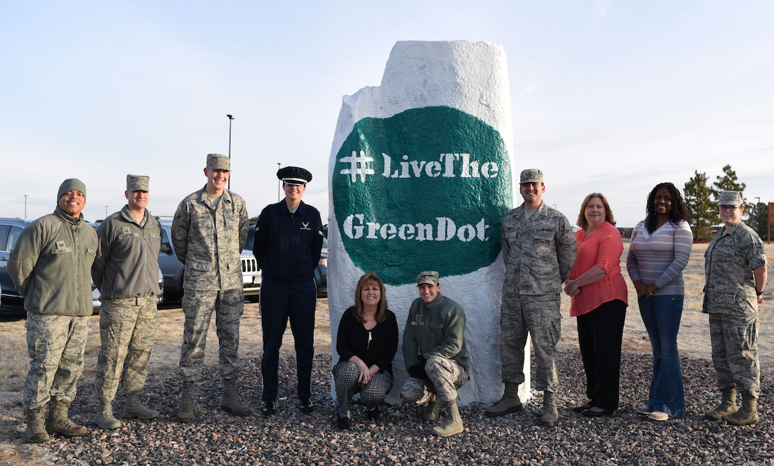 Members of Team Buckley's Green Dot facilitator team pose next to the base spirit rock March 13, 2017, on Buckley Air Force Base, Colo. Green Dot, a five-year strategy plan for the Air Force to reduce interpersonal violence, has completed its first year on Buckley AFB. (U.S. Air Force photo by Airman Holden S. Faul/ Released)
