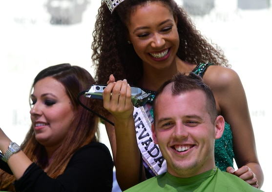 Miss Nevada Teen USA Alexis Smith, shaves 2nd Lt. Kyle's hair for a fundraiser, March 11, 2017, in Las Vegas. Kyle is a 15th Attack Squadron MQ-1 Predator pilot. He and other members of his unit shaved their heads in support of children who have been diagnosed with cancer. (U.S. Air Force photo/Senior Airman Christian Clausen)