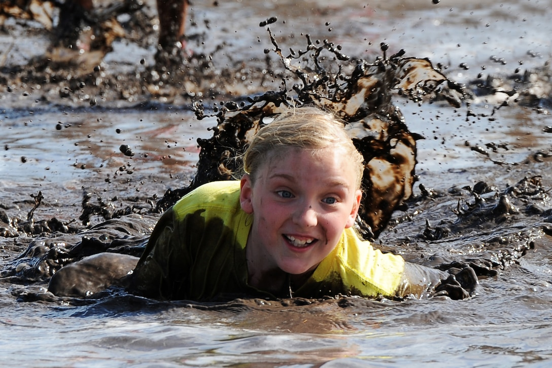 A military child crawls through mud