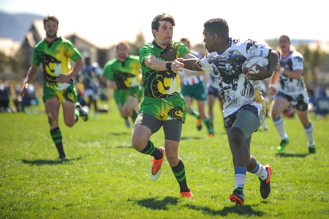 Malcolm Gilliam, a wing on the Air Force men's rugby sevens team, stiff arms a defender during a Las Vegas Invitational match in Las Vegas, March 2, 2017. The tournament marked the first game action of the Air Force rugby program's season, which will culminate in the Armed Forces Championship. (U.S. Air Force photo by Staff Sgt. Siuta B. Ika)