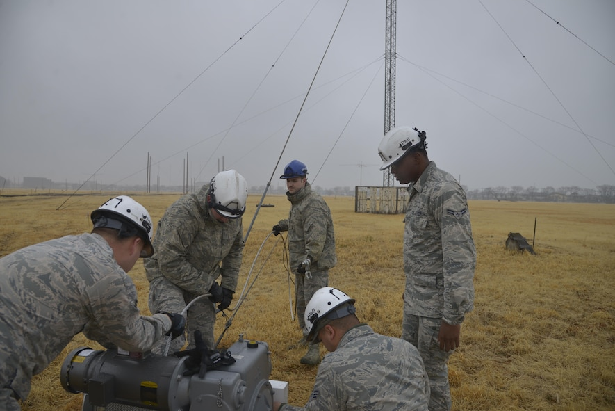 Members of the 374th Communication Squadron Cable and Antenna System Unit set up the winch line at the Tokorozawa Communication Site, Japan, March 14, 2017. The Airmen took the rotatable log periodic antenna down over a three day period to allow a road to be placed through the site for emergency vehicles to have a quicker response time. (U.S. Air Force photo by Staff Sgt. David Owsianka)