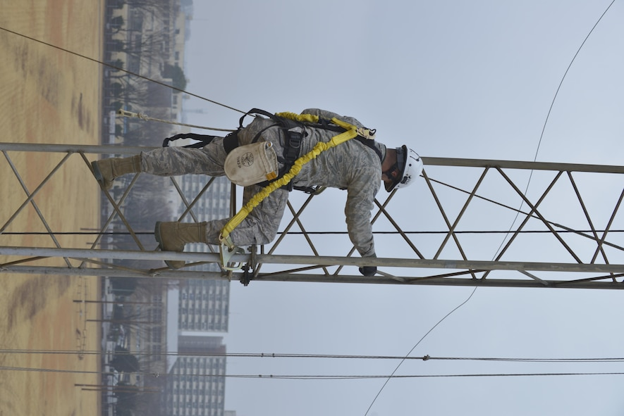 Senior Airman Javier Calvo, 374th Communication Squadron cable and antenna system technician, climbs up a rotatable log periodic antenna tower at the Tokorozawa Communication Site, Japan, March 14, 2017. Calvo wore a safety harness to prevent the possibility of falling and ensured he had three points of contact throughout the climb. (U.S. Air Force photo by Staff Sgt. David Owsianka)