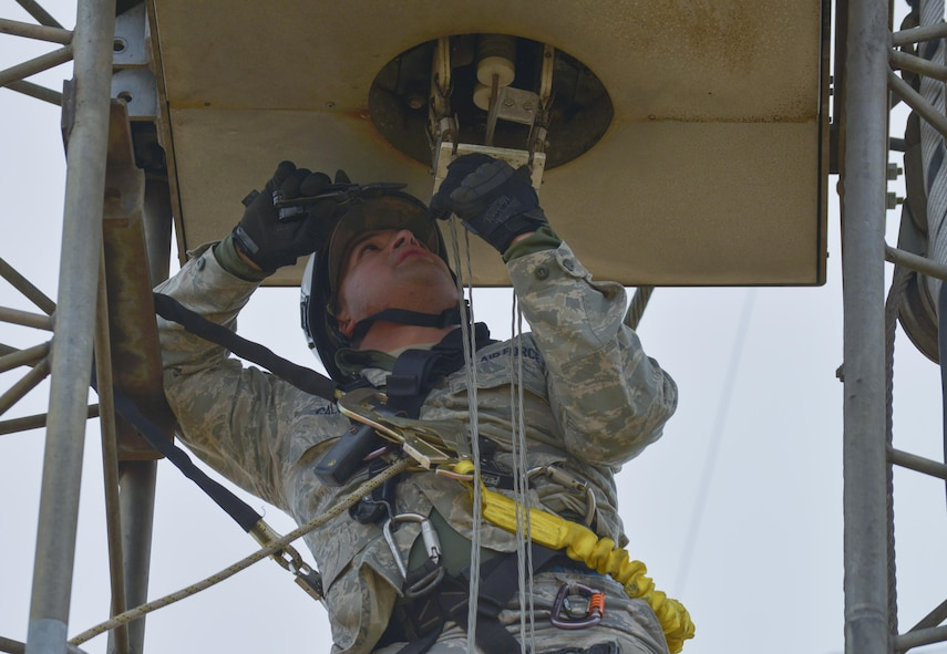 Senior Airman Javier Calvo, 374th Communication Squadron cable and antenna system technician, works to remove a transmission line on a rotatable log periodic antenna at the Tokorozawa Communication Site, Japan, March 14, 2017. The transmission line provides the transmission frequency from the control site to the receiving site. (U.S. Air Force photo by Staff Sgt. David Owsianka)