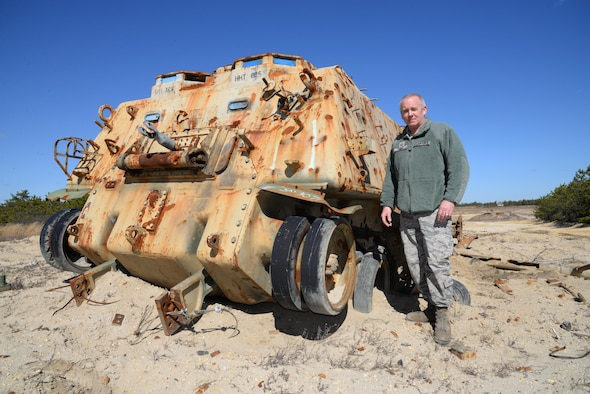 A picture of U.S. Air Force Master Sgt. Bryan ONeill, range section chief at the 177th Fighter Wing Det. 1 - Warren Grove Bombing Range in Burlington County, N.J., standing beside a demilitarized M88A1 armored recovery vehicle.