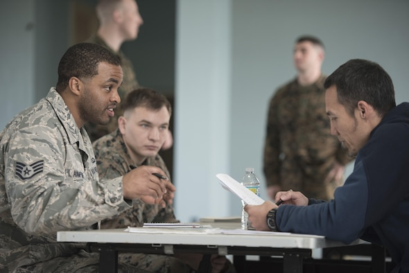 U.S. Air Force Staff Sgt. Lewis Hampton and Nichalos Apsens, 18th Contracting Squadron contracting officers, portray the roles of a contracting officer and a vendor during an operational contracting support joint exercise Jan. 24, 2017, at Camp Foster, Japan. In this scenario, contractors met with vendors, figured out how to communicate in Japanese without translators and negotiated contracts within 24-hours. (U.S. Air Force photo by Senior Airman Omari Bernard)
