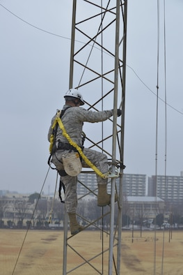 Senior Airman Javier Calvo, 374th Communication Squadron cable and antenna system technician, climbs up a rotatable log periodic antenna at the Tokorozawa Communication Site, Japan, March 14, 2017. Calvo wore a safety harness to prevent the possibility of falling and ensured he had three points of contact throughout the climb. (U.S. Air Force photo by Staff Sgt. David Owsianka)