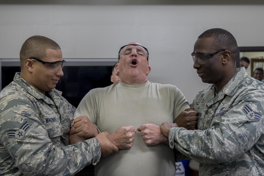Col. Kenneth Moss, 374th Airlift Wing commander, reacts to getting tased during a 374th Security Forces Squadron less-lethal weapons demonstration March 15, 2017, at Yokota Air Base, Japan. Moss volunteered to be part of the demonstration to experience and understand more of what SFS members go through and to show his support. (U.S. Air Force photo by Airman 1st Class Donald Hudson)