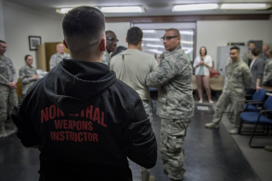 Tech. Sgt. Justin McDonald, 374th Security Forces Squadron NCO in charge of security forces training, counts down to tase an Airmen during a less-lethal weapons demonstration, March 15, 2017, at Yokota Air Base, Japan. McDonald is one of two SFS members to attend the Inter-service Nonlethal Individual Weapons Instructor Course. (U.S. Air Force photo by Airman 1st Class Donald Hudson)