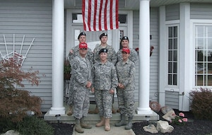 Members of the Clemens family, with more than 120 years of military service, stand in front of the family home in Port Clinton, Ohio, after three of them returned from overseas deployments. Pictured are retired Senior Master Sgt. Ken Clemens (clockwise from front row, left), Col. Barb Herrington-Clemens, Capt. Chelsea Migura, Staff Sgt. Rich Clemens, Staff Sgt. Drew Clemens and Sgt. 1st Class Zach Migura.