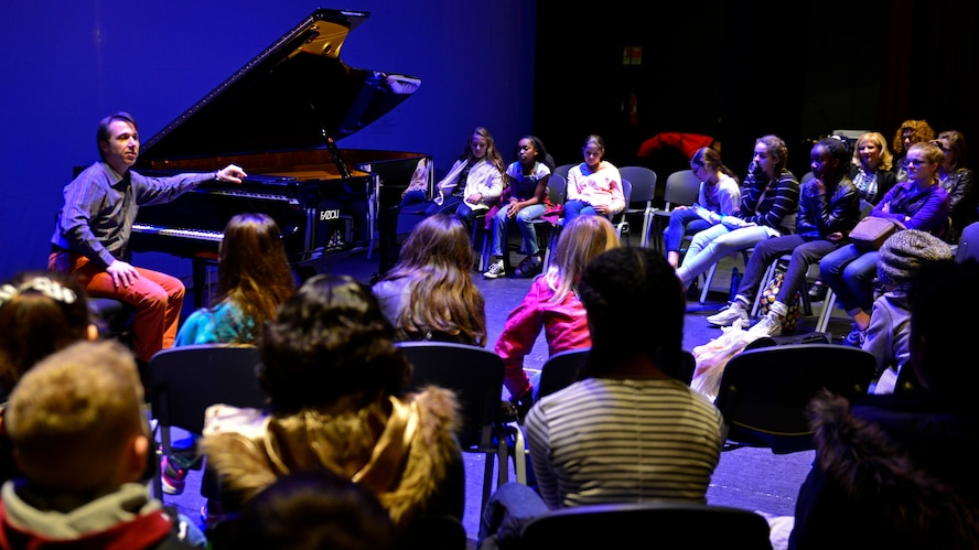 Maurizio Baglini, Italian pianist, speaks to an Aviano Middle High School sixth-grade class about classical music during their visit to the Pordenone Theater, March 10, 2017. Baglini played various compositions from Bach, Mozart and Beethoven during the student's visit. (U.S. Air Force photo by Senior Airman Cary Smith)