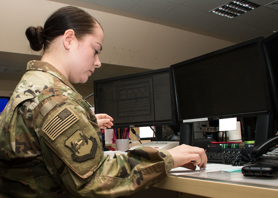 """Senior Airman Laurin Curtis, a 386th AEW emergency action controller, works at a console in the command post March 15, 2017. """"One thing I think that I'm really fortunate in is to be able to see the mission as a whole from a bird's eye view...,"""" said Curtis. (U.S. Air Force photo illustration/Senior Airman Andrew Park)"""